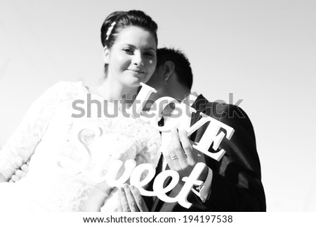 Black and white bride and groom having fun and posing with Sweet Love letters in sunlight