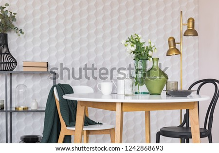 Black and white chair at wooden table in dining room interior with flowers and gold lamp. Real photo #1242868693