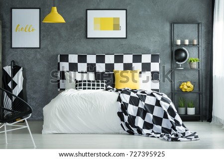 Black and white checkered bedsheets and yellow pillow on bed in bedroom with metal shelf