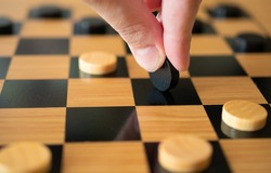 Black and white checkers are laid out on the playing Board, ready to play a game, the hand plays black checkers and makes a move: concept of Board games, entertainment, background, games at home for t