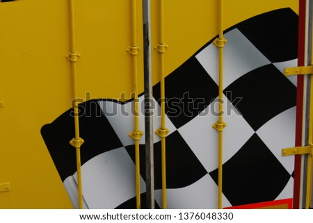 Black and white chequered flag which symbolises race winner, shown here against bright yellow background. Champions are winners. Winners are champions. Small local races or full international races. #1376048330