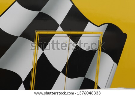 Black and white chequered flag which symbolises race winner, shown here against bright yellow background. Champions are winners. Winners are champions. Small local races or full international races. #1376048333