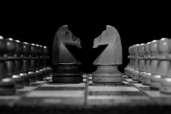 Black and white chess faceoff of both knights horses on top of a chess board in front of a dark background surrounded by pawns of both sides