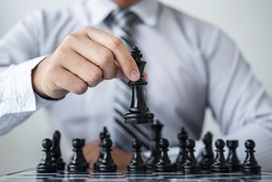 Black and White chess with player, Hands of businessman thinking to moving chess figure in competition and planning strategy to success play for win.