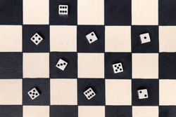 Black and white chessboard with dice showing assorted numbers placed on the black squares in an overhead background view conceptual of entertainment, board games and gambling