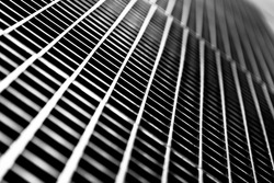 Black and white close up of a sidewalk subway grate with shallow depth of field.