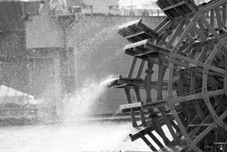 black and white close up of an old paddle wheel on the river