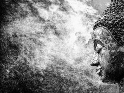 Black and white close up of side face of Buddha statue on abstract background