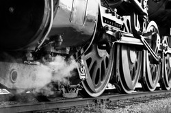 Black and White close-up of wheels on an antique steam train waiting to leave the station