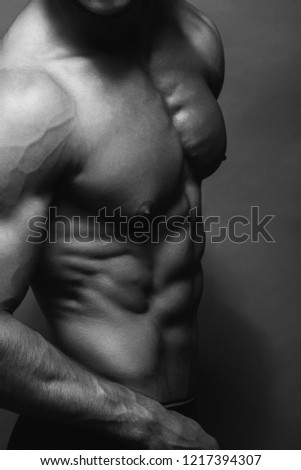 Black and white close up portrait of fitness athletic young boy showing muscles. Bodybuilding. Strong man posing on background.