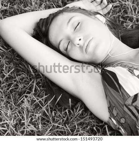 Black and white close up portrait view of an attractive young woman laying on textured green grass listening to music with her mp3 player with her eyes closed during summer.