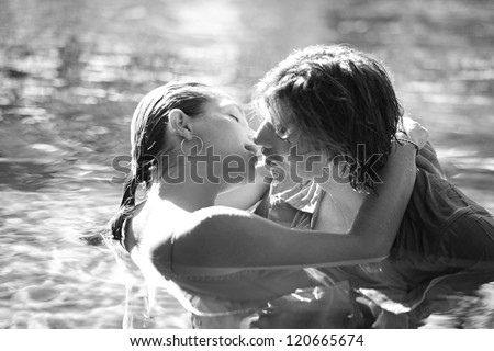 Black and white close up view of a sexy young couple submerged in a swimming pool while dressed, hugging and kissing while on a tropical destination vacation.