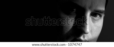 Black and white closeup of a man's face, with the right side mostly hidden in shadow.