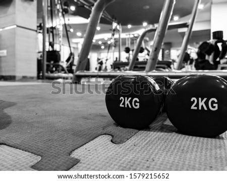 Black and white closeup of small 2 kg dumbbells in blue color on rubber ground in a well equipped interior gym for weight loss and strength training