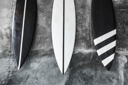 Black and white color surf board on gray concrete wall background. Contemporary interior design of cafe in minimalist style. Dark shabby texture.