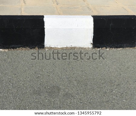 Black and white concrete curb with asphalt road  close-up #1345955792