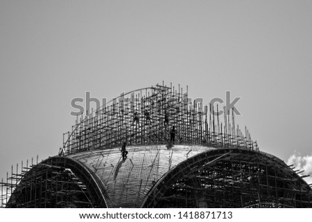 Black and white construction silhouette. Workers on the top of the construction. Working on the dome of a mosque. #1418871713