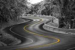 Black and white curve way of asphalt road in nature with yellow line.