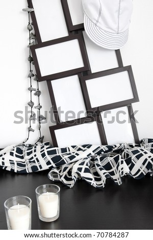Black and white decor: photo frames, clothing and candles.
