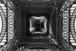 Black and white detail of the Eiffel Tower in Paris, France, shot from below.