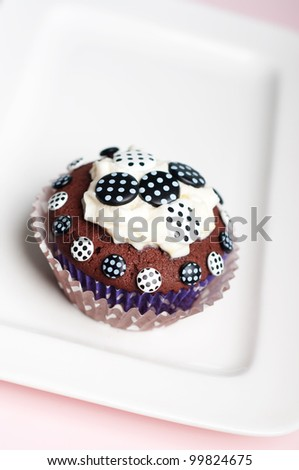Black and white dotted chocolate cupcake on a white plate