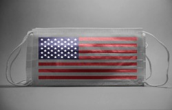 Black And White Dramatic atmosphere with surgical mask with american flag,usa flag text printed on it.Impact of pandemic virus to usa.Covid -19 spread around USA