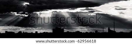 Black and white dramatic cloudscape with rays of light piercing through the clouds.
