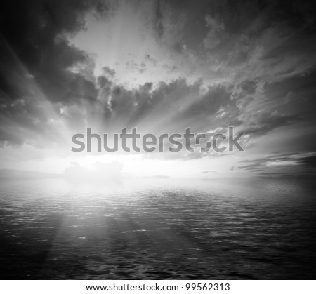 black and white dramatic landscape with water with waves and cloudy sky at sunset
