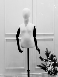 Black and white dummy with black hands on white framed background with small Christmas tree in corner of shot. Minimal winter backdrop. Monochrome Christmas background with creative mannequin.