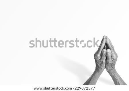 Black and white elder woman hands praying.