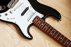 Black and white electric guitar. Top view of the electric guitar body against of the wooden floor. Music equipment. Musical instruments.