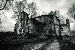 Black and white exterior shot. Gothic ruins of a medieval church with long shadows cast by the trees at dusk.