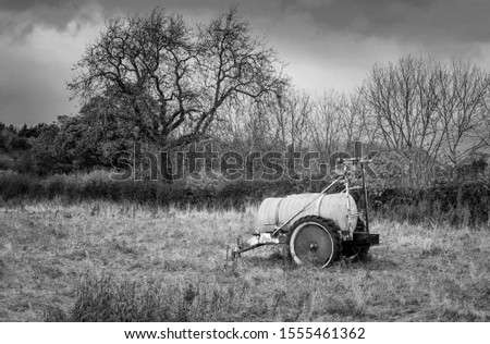 Black and White Farming scene with farming equipment in foreground and trees in background