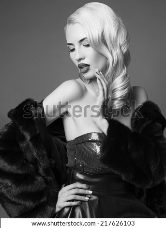 black and white fashion photo of sexy woman with blond hair in elegant black fur coat posing in studio