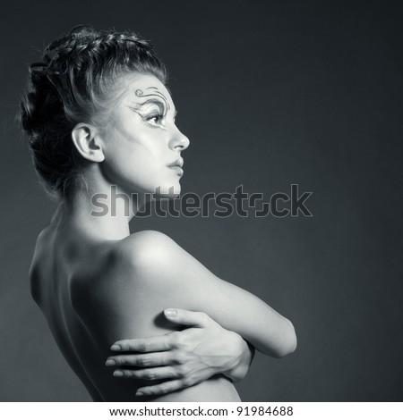 Black and white fashion portrait of beautiful woman posing on black background