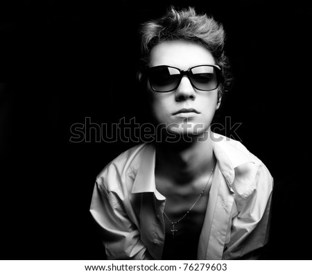 Black and white fashion portrait of the young guy dressed in shirt. Sunglasses