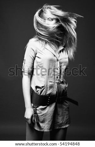 Black and white fashion portrait of young woman with flying hair on dark background