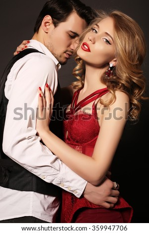 black and white fashion studio photo of beautiful impassioned couple, wears elegant clothes, embracing each other