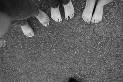 Black and white feet in cobblestone. Three pairs of feet. Family, unity. Black and white.