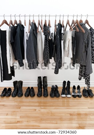 Black and white female clothes on hangers and shoes on a wooden floor.