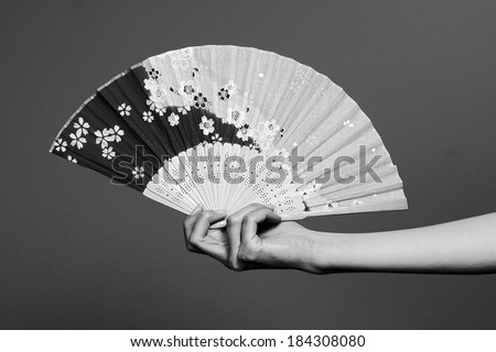 black and white feminine hand and a Japanese fan