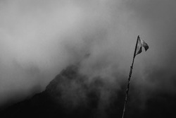 Black and white fine art shot of  a flag waving in the mountains surrounded by clouds