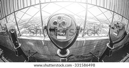 Black and white fisheye lens toned photo of tourist binoculars over Manhattan, New York City, USA.
