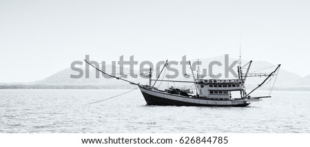 black and white fishing boat on the sea #626844785