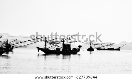black and white fishing boat on the sea #627739844