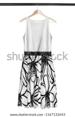 752e5a70972 Black and white flared sundress hanging on wooden clothes rack isolated  over white  1167132643