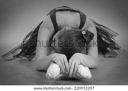Black and white foto of young stretching ballerina
