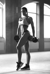 Black and white frontview of athletic sporty woman posing with dumbbells in spacy gym with panoramic windows. Having strong, fit body with heatlthy tanned skin and muscles. Doing fitness exercises.