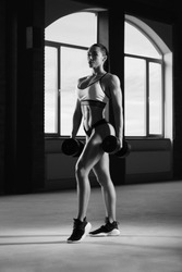 Black and white frontview of athletic woman posing with dumbbells in spacy gym with panoramic windows. Having strong, fit body with heatlthy tanned skin and muscles. Doing fitness exercises.