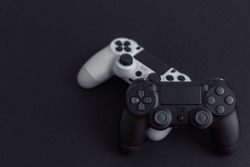 Black and white gamepads on a black background. Minimalism. Selective focus. Free space for text.